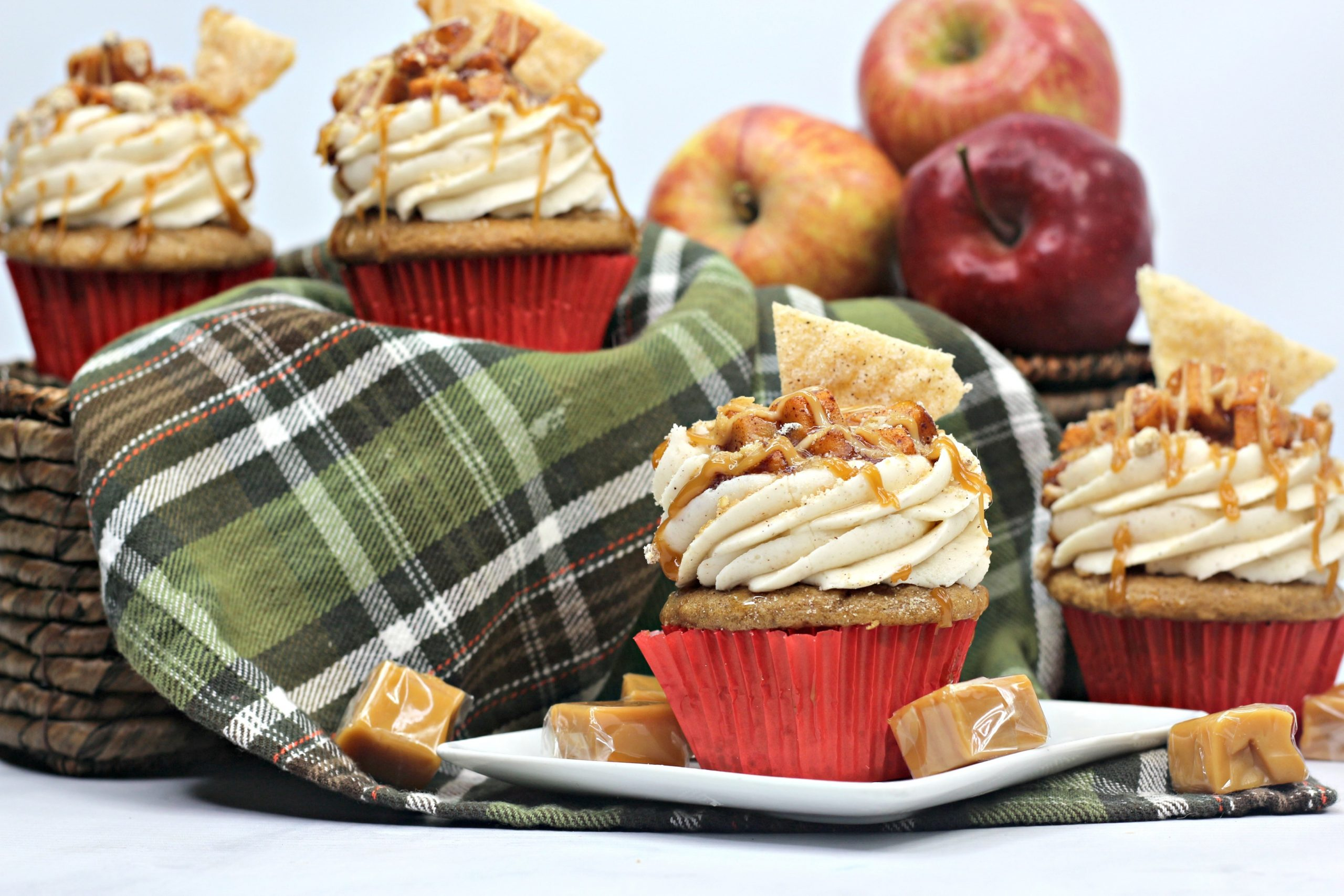 Apple Pie Cupcake with some caramel candies all around them.