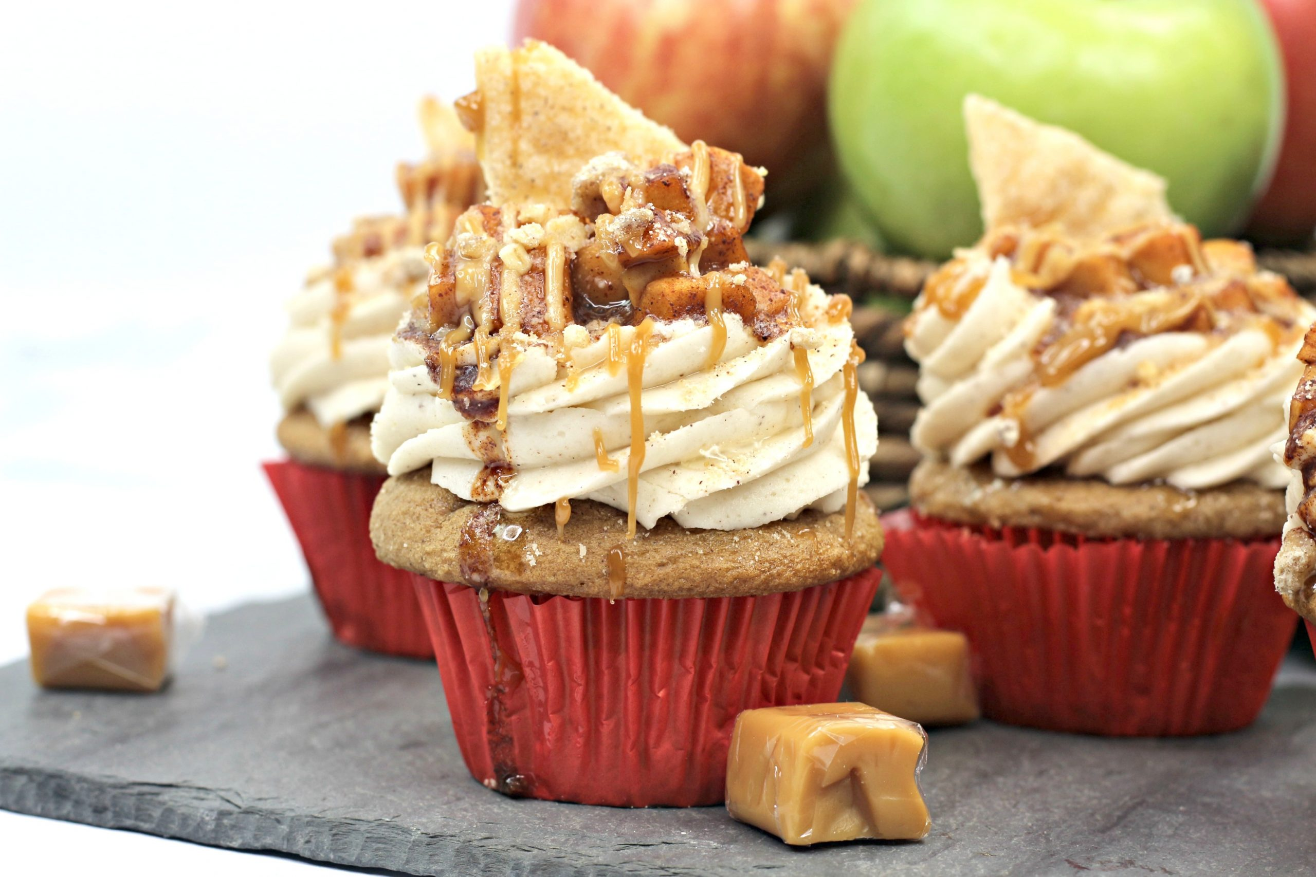Apple Pie Cupcakes with a basket of apples behind them.
