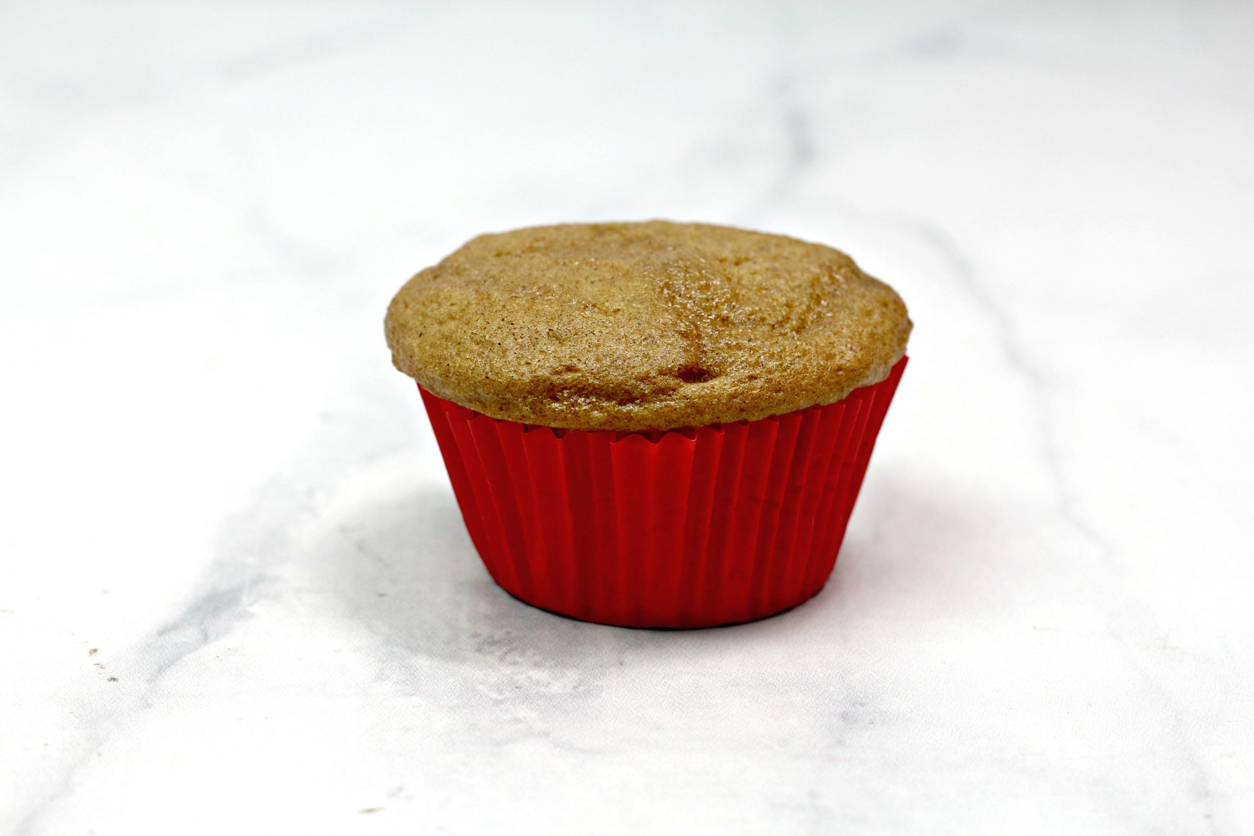 A finished and bare cupcake in a cupcake liner.