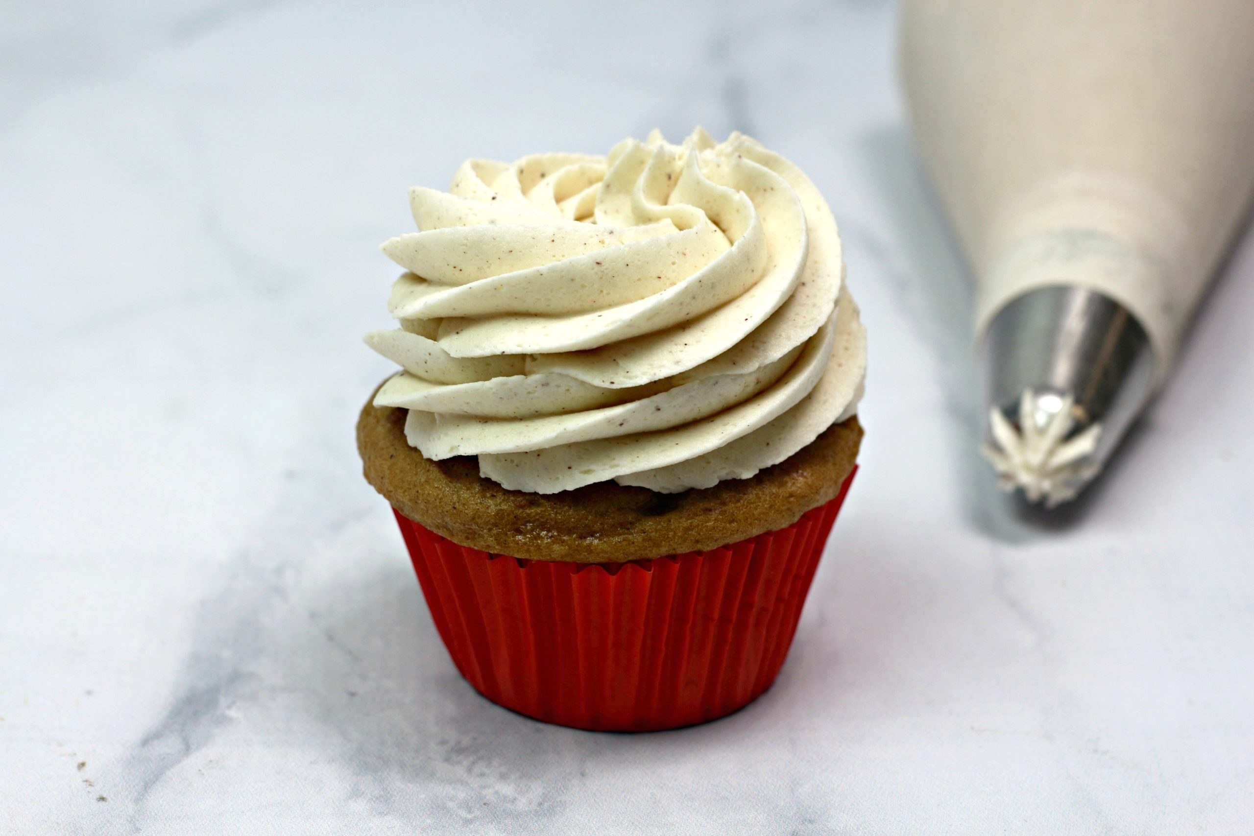 Piping the frosting on baked cupcake.