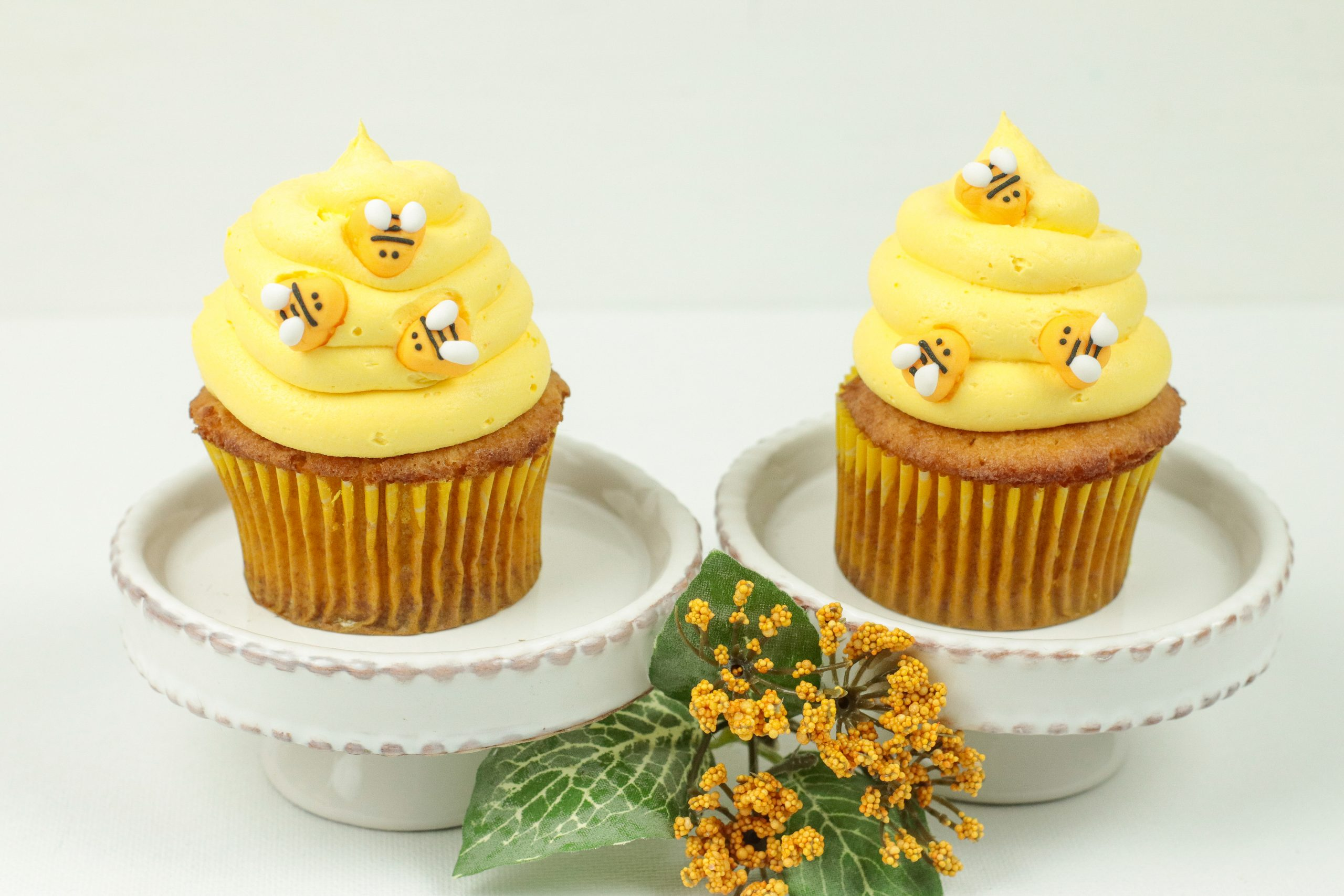 Two Honey Cinnamon Bumblebee Cupcakes on two separate serving dishes.