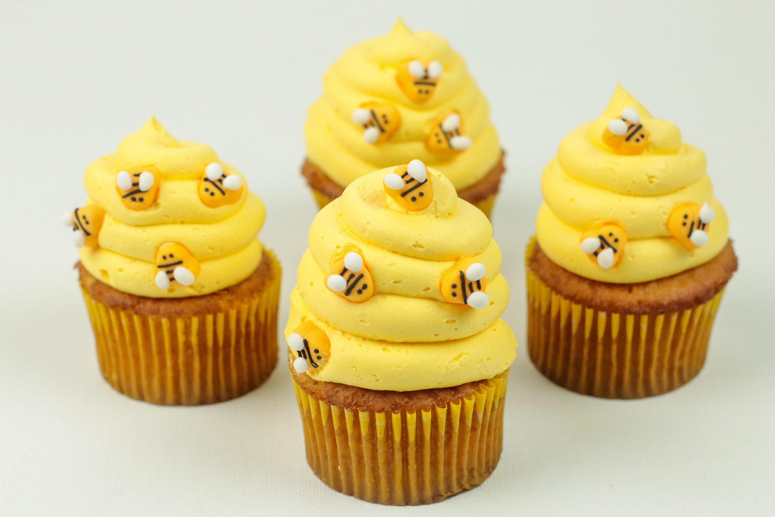 Four Honey Cinnamon Bumblebee Cupcakes on a table.