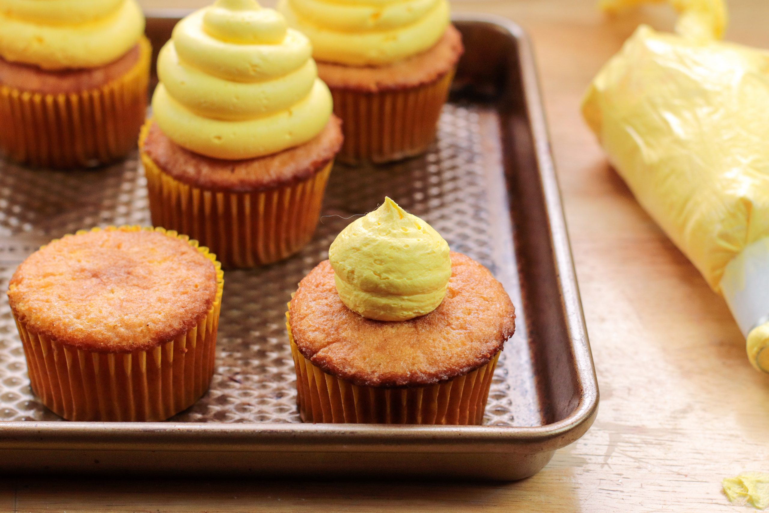 Piping the cupcakes with frosting.
