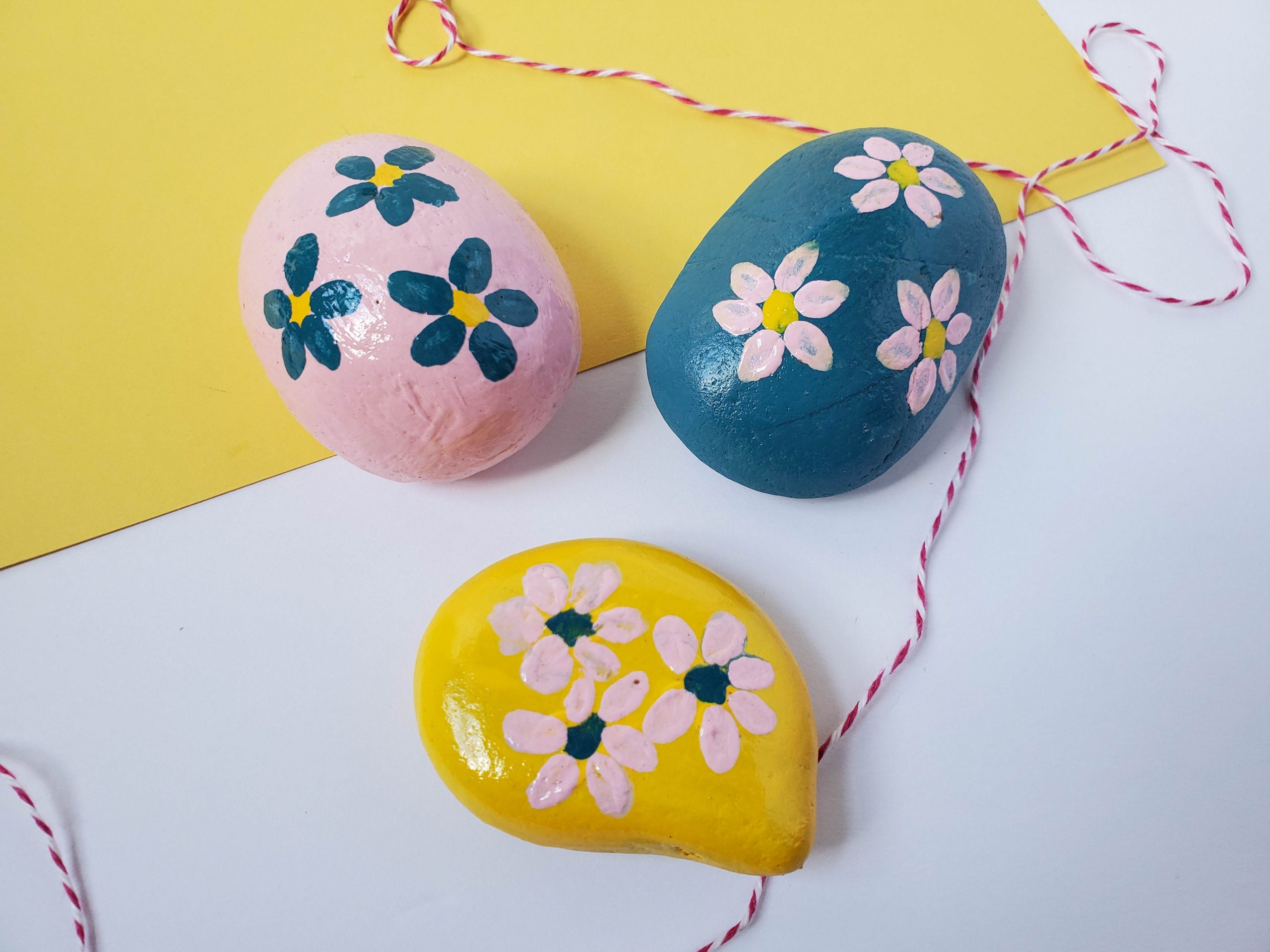 The painted rocks by a yellow piece of paper.