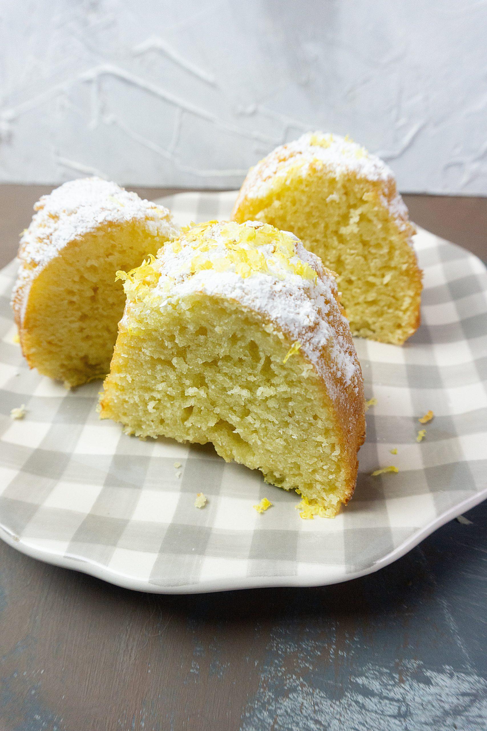 Meyer Lemon Bundt Cake cut into pieces on a serving plate.