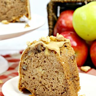 A slice of Bundt Cake full of apples, walnuts and caramel and topped with glaze.