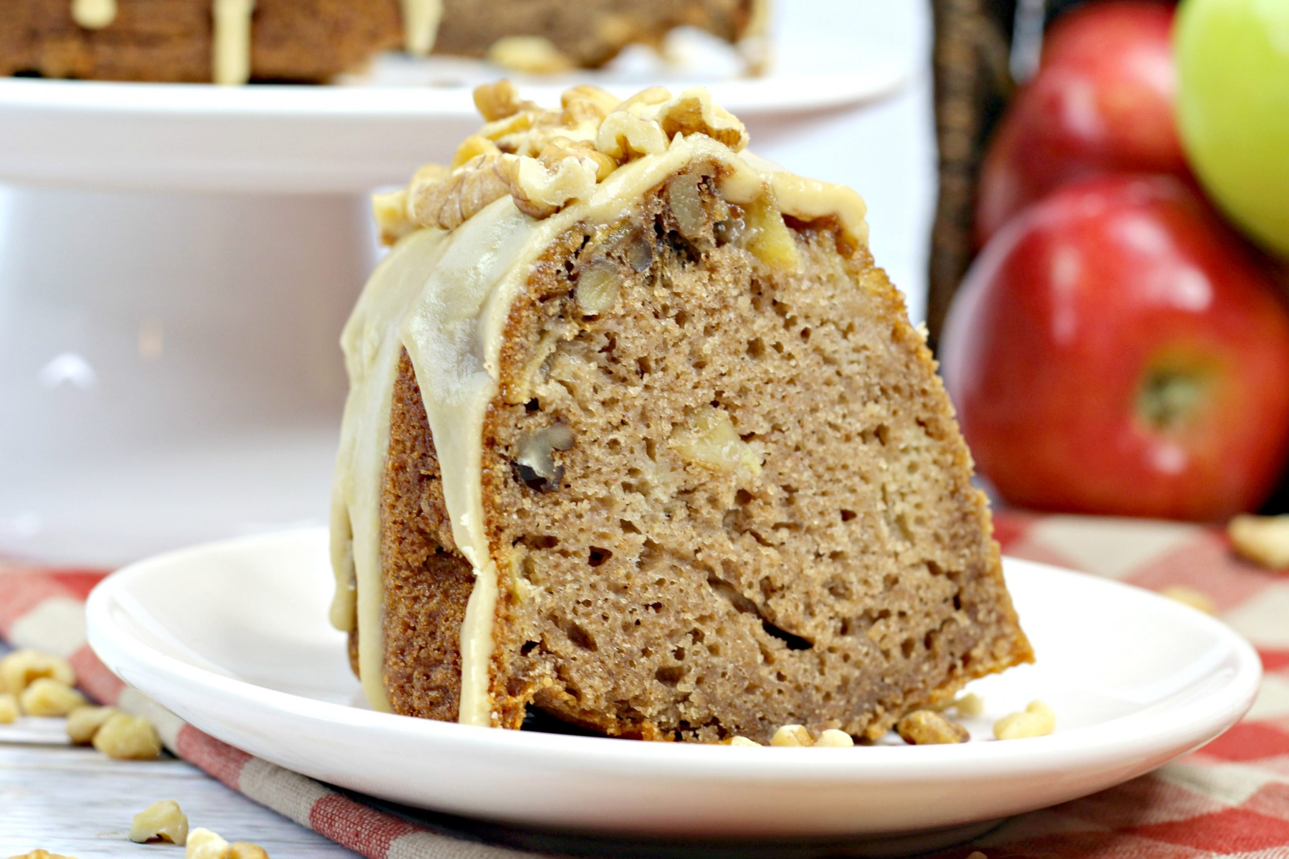 A slice of the caramel apple Bundt cake topped with a glaze and walnuts.