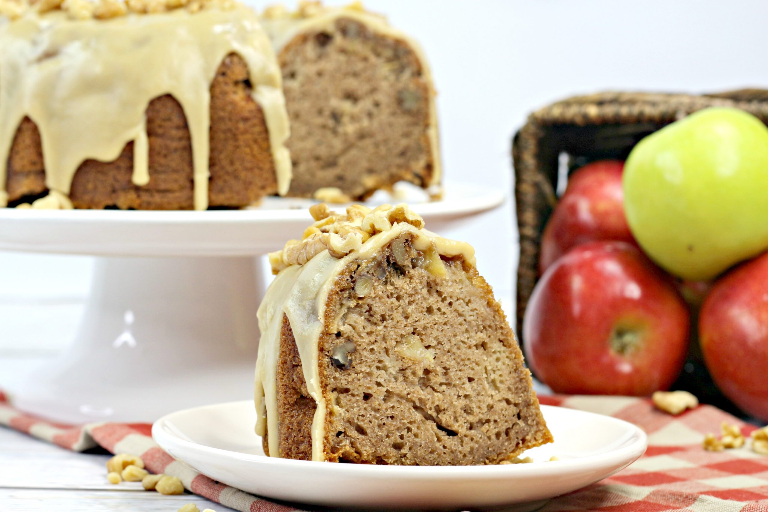A slice of the caramel apple Bundt with the rest of the cake behind it.