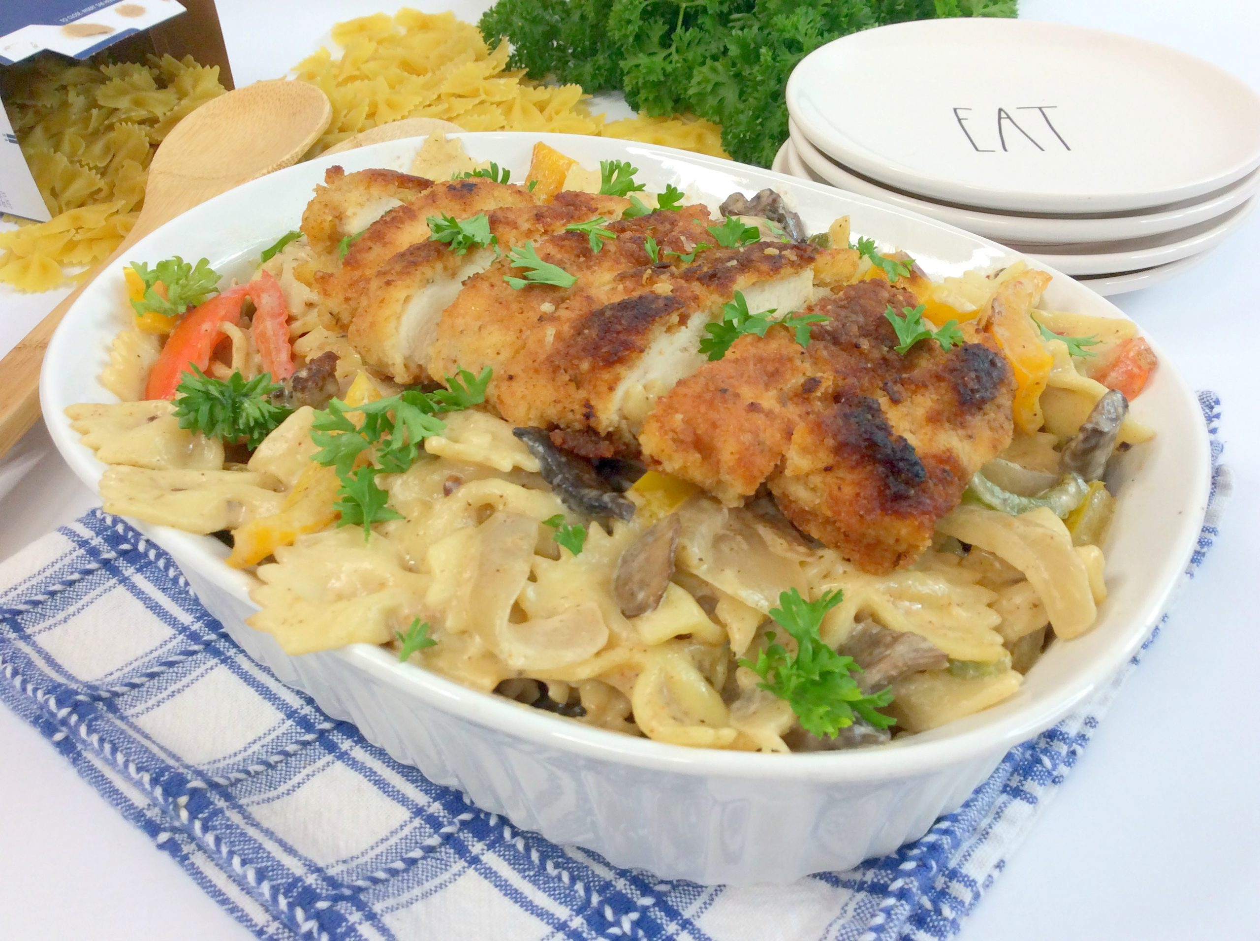 The chicken pasta in a dish on top of a cloth.