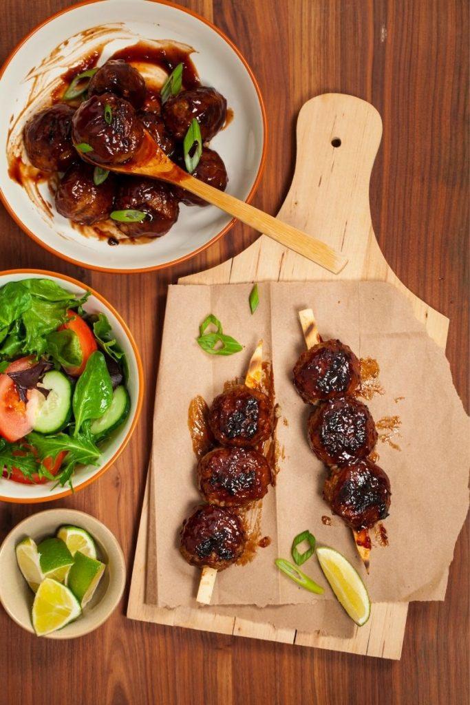 BBQ meatballs on a brown cutting board