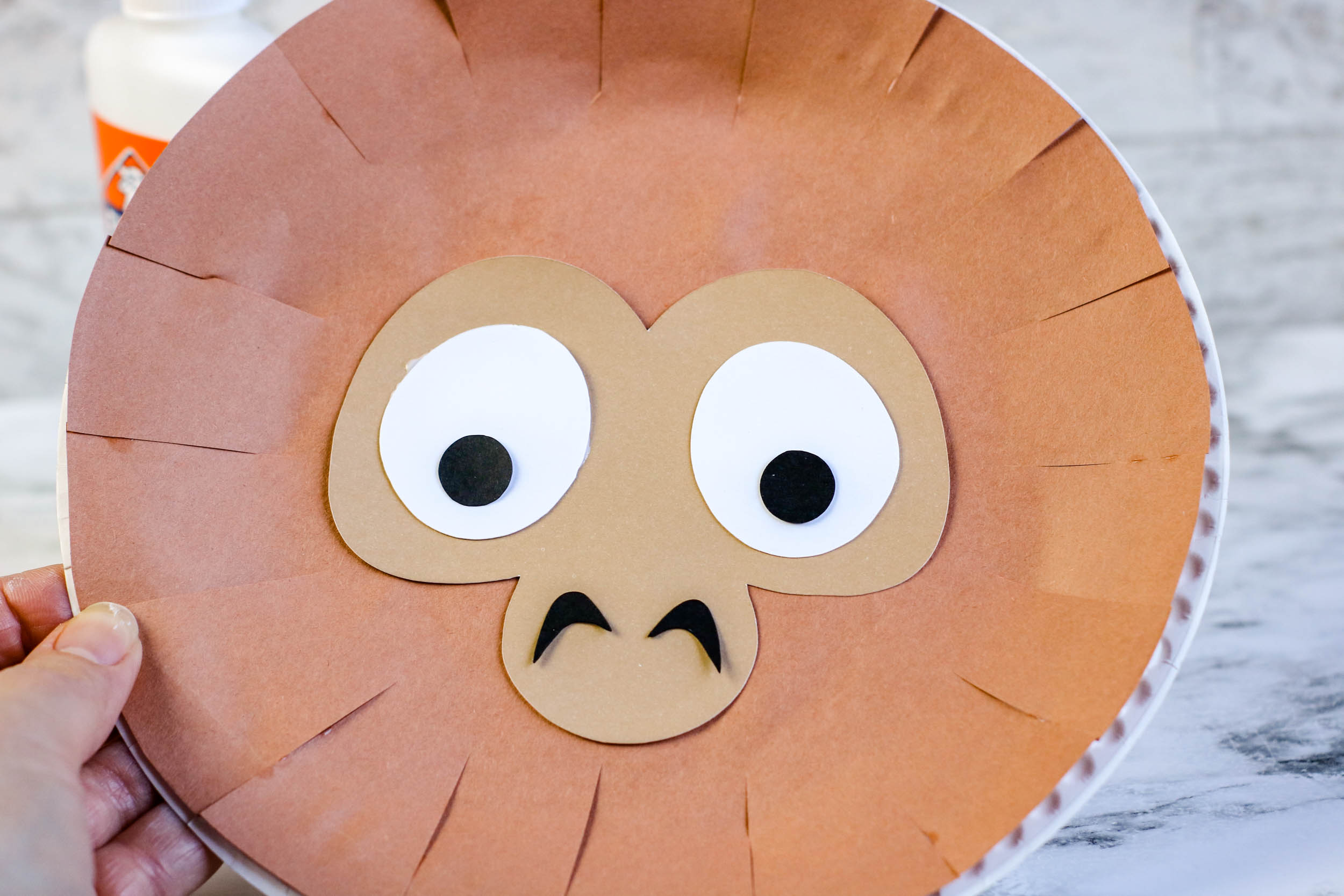 Gluing the materials on the Paper Plate Monkey Puppet