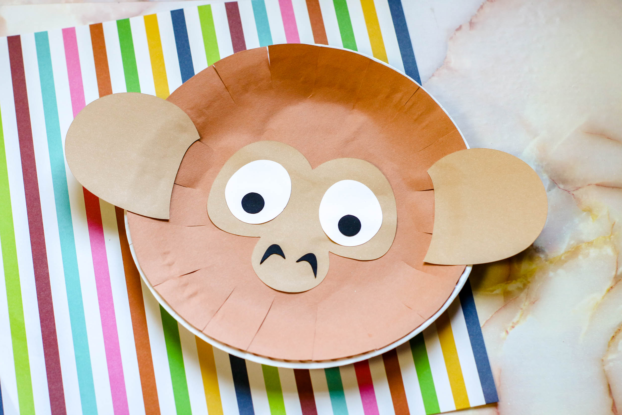 Paper Plate Monkey Puppet on a colorful piece of paper.