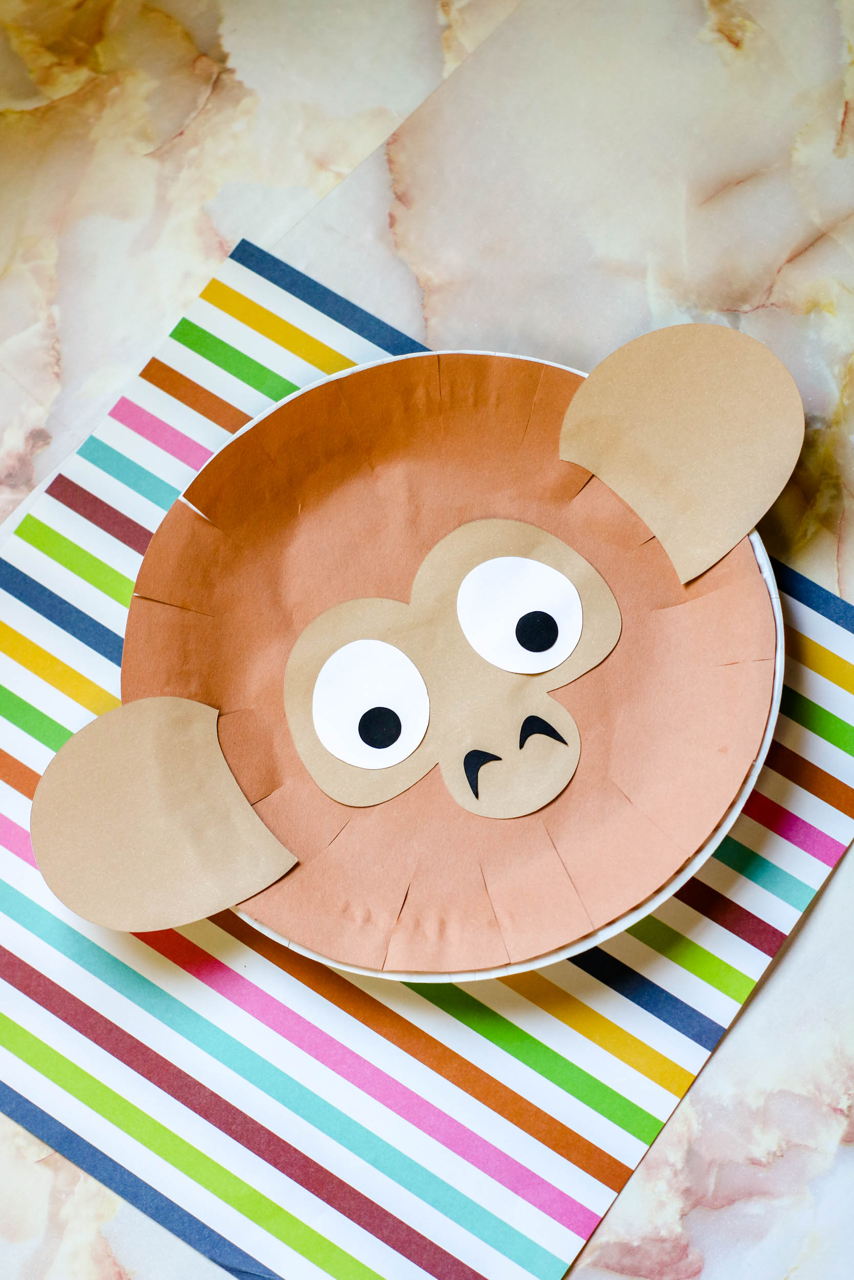 Paper Plate Monkey Puppet on a marbled table.