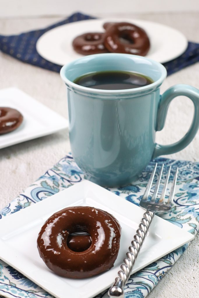 chocolate donut on a white plate with a coffee cup