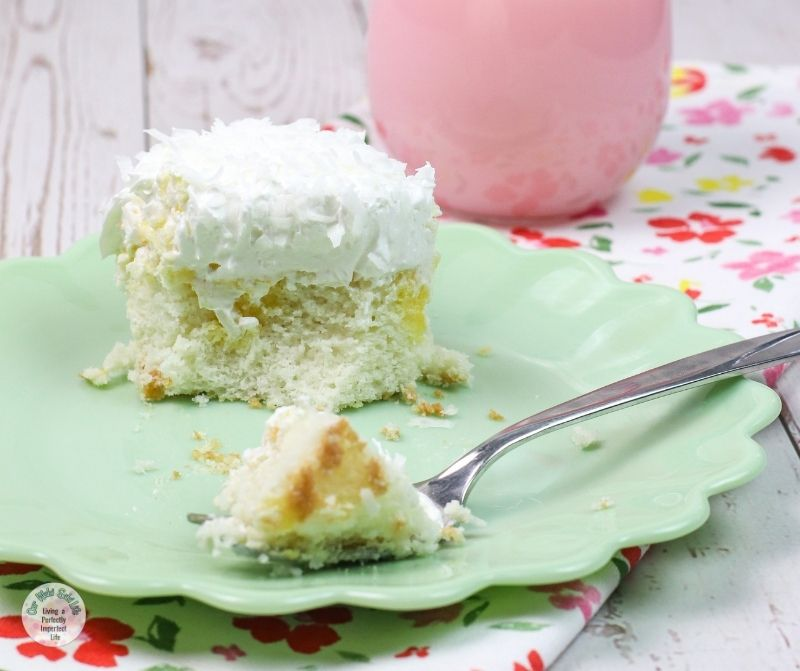 A piece of coconut poke cake with a glass of strawberry milk.