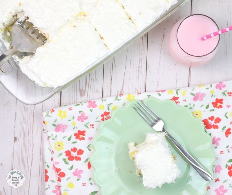 A piece of the coconut cake on a green serving dish.