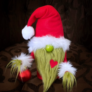 Grinch gnomes on a brown pillow.