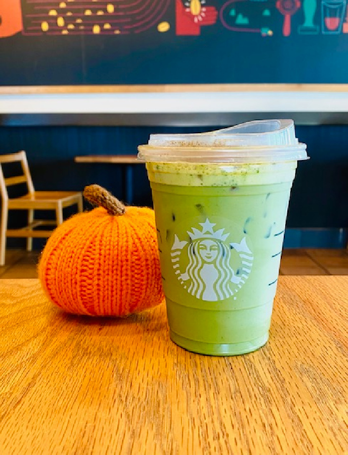 The latte and a pumpkin on a wooden table.