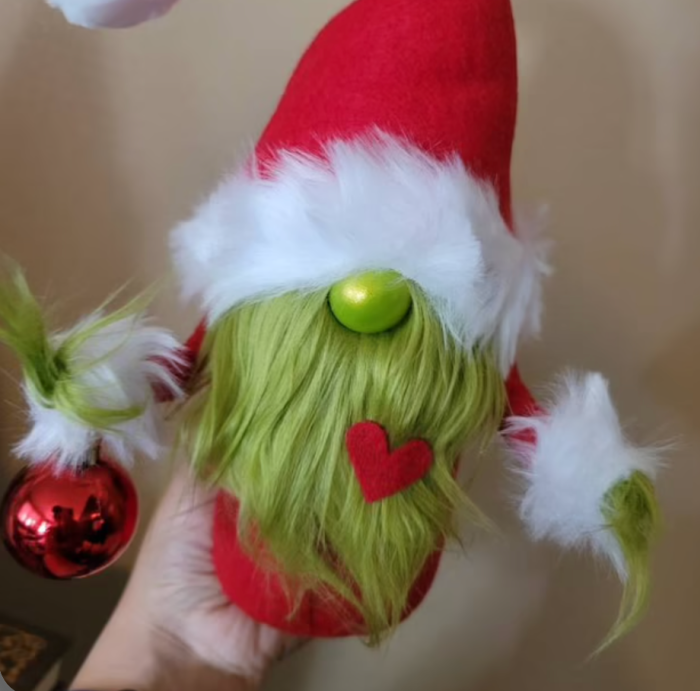 Someone holding up the Grinch gnome.