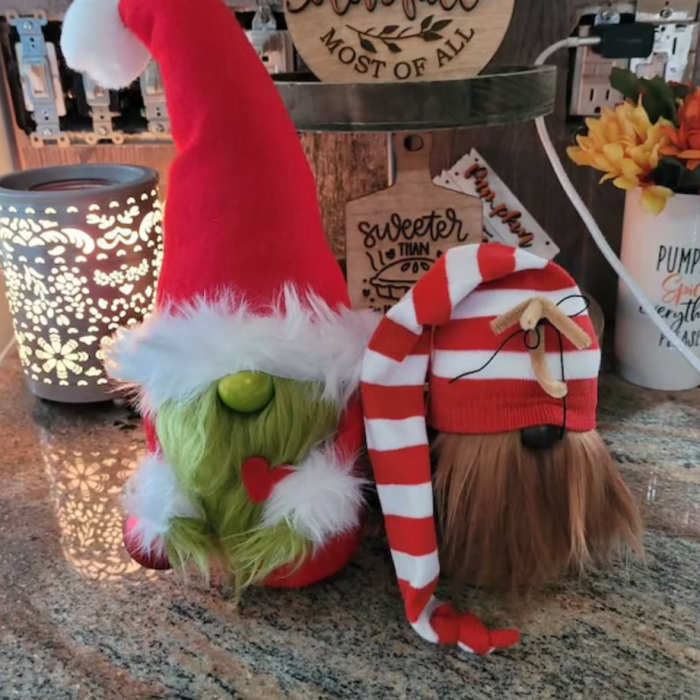 The Max and Grinch gnome on a marble table.